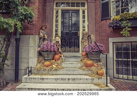 residence front entrance on Halloween. creepy decorations. black door and pumpkin, flowers and scarecrows on the stairs