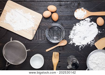 flour sprinkled with different kitchen tools on dark black background. Baking ingredient Top view
