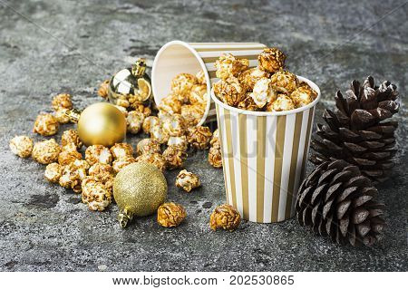 Appetizing golden caramel popcorn in paper striped cups in the New Year's interior with fir cones, New Year's golden balls on a gray stone modern background. Selective focus