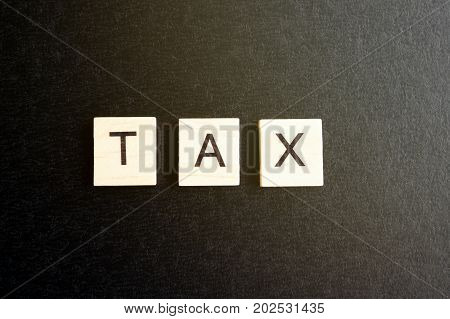 Tax Word On Wood Blocks With Black Background With Filter And Analog Effect
