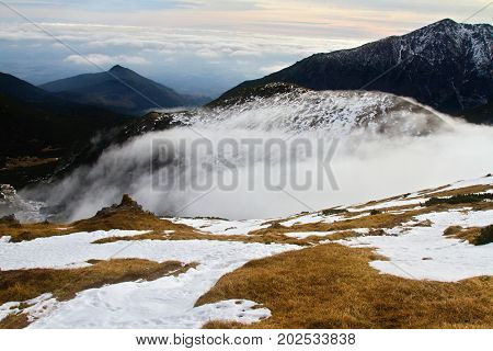 High Tatras peaks and valleys. Landscape with trees and fog. Autumn inversion in Slovakia. Freeze land. Low sky scenery.
