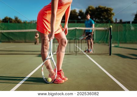 Couple with tennis rackets plays on outdoor court