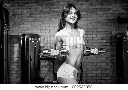 Beautiful sexy athletic young brunette Caucasian girl working out training arms in the gym gaining weight pumping up muscles bicep and tricep with dumbbells and on machines gaining weight and poses