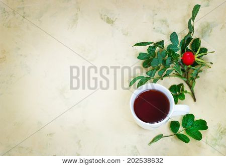 Tea from a dogrose in a mug on a light background with fruits.