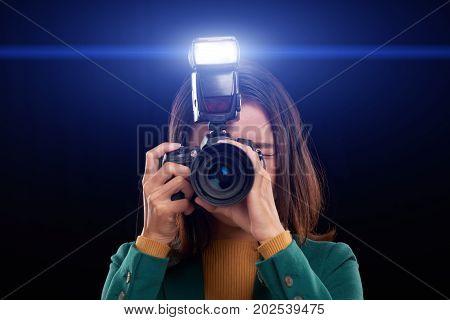 Female photographer taking photos with flash, isolated on dark