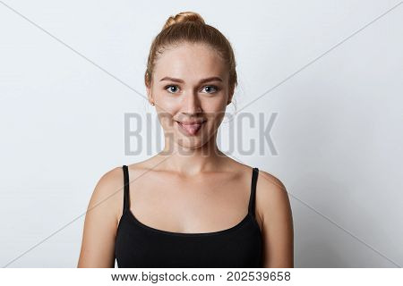 Indoor Shot Of Funny Blonde Female With Hair Knot, Showing Tongue While Arguing With Someone, Trying