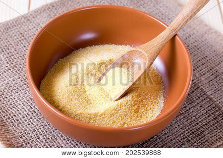 Semolina in a bowl with a wooden spatula