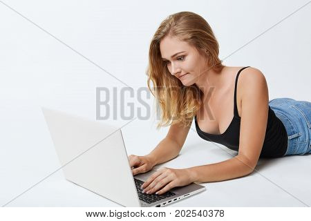 Restful Female With Long Blonde Hair, Lying On White Floor In Front Of Opened Laptop, Messaging With
