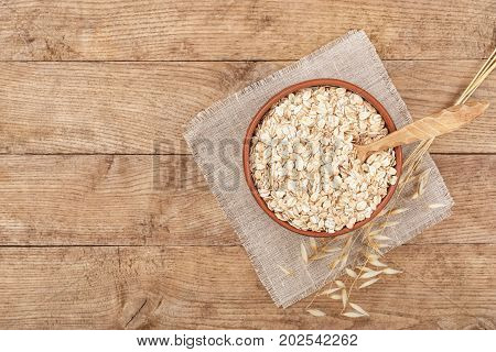 oat flakes in bowl with spoon near and oat ears on wooden table top view. Uncooked oatmeal. Copy space