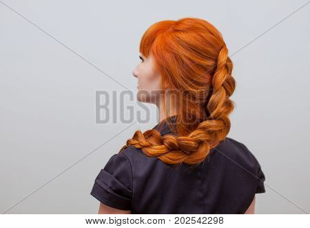 Beautiful girl with long red hair braided with a French braid in a beauty salon. Professional hair care and creating hairstyles.
