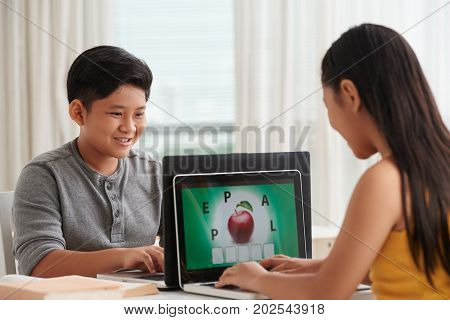 Children in school learning new English game view game on laptop