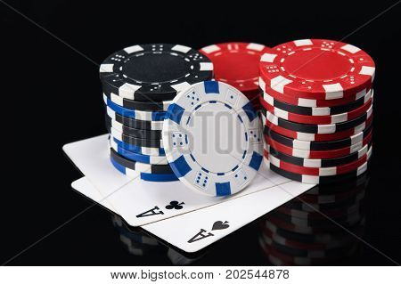 two large playing cards with poker chips on a dark background