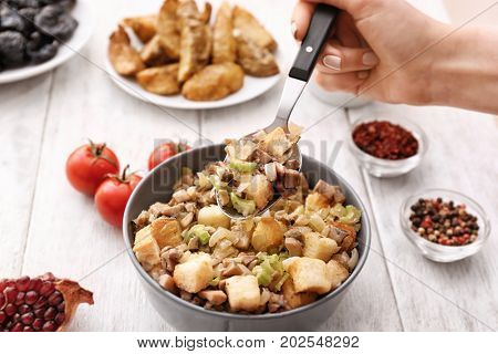 Woman taking appetizing turkey stuffing with spoon