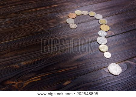 question mark from coins of different countries on a wooden background
