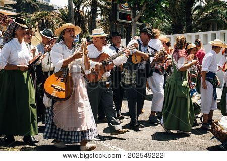 Puerto de la Cruz Tenerife Canary Islands - May 30 2017: Canaries people dressed in traditional clothes walk along the street sign and play musical instruments. Local residents of Tenerife celebrate the Day of the Canary Islands.