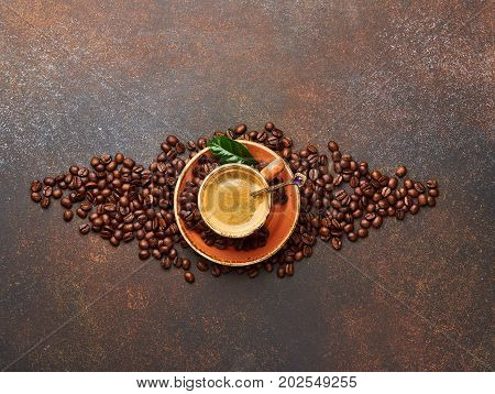 Coffee beans with cup of cofee on brown concrete table with copy space for design.