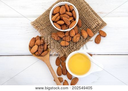 Close up almond oil in the bottle and almond seed in white cup for oil massage and spa treatment ingredient on white wooden table background top view or over head shot with copy space