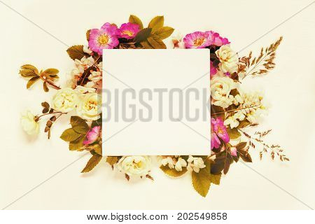 Scrapbook page of wedding or family photo album frame with wild rose white flowers and green leaves on light wooden background; top view flat lay overhead view. Mocap. Toned image