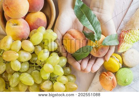 Hands of a young woman holding a peach's. Woman making a choice between sweets and fruits made a choice in favor of fruits and holding peaches. Unhealthy vs healthy food top view.
