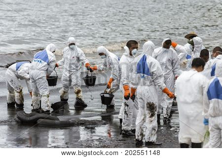 RAYONG THAILAND - JULY 31 2013: Workers remove and clean up crude oil spilled from Prao Bay on July 31 2013 in Samet Island Rayong Thailand