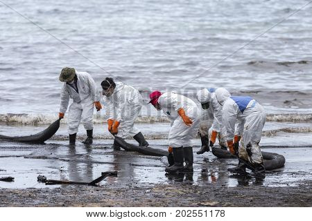 RAYONG THAILAND - JULY 31 2013: A Worker in biohazard suits used Oil Containment boom as cleaning crude oil spilled from the beach of Samet Island on July 31 2013 in Rayong Thailand.