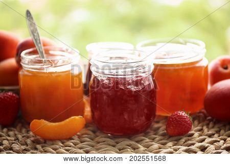 Apricot and berry jams in jars on wicker mat outdoor