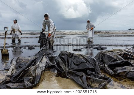 RAYONG THAILAND - JULY 31 2013: Workers remove and clean up crude oil spilled with absorbent paper from Prao Bay on July 31 2013 in Samet Island Rayong Thailand