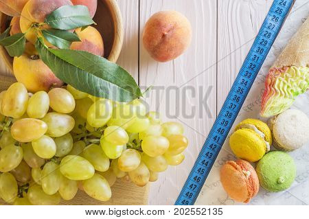 Choosing between Fruits and Sweets. Healthy versus unhealthy food. Weight Loss. Unhealthy tempting cakes and healthy fruits. Healthy and unhealthy food is divided by a measuring tape.