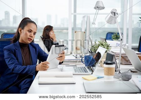 Filipino business woman reading information on her tablet when working in office