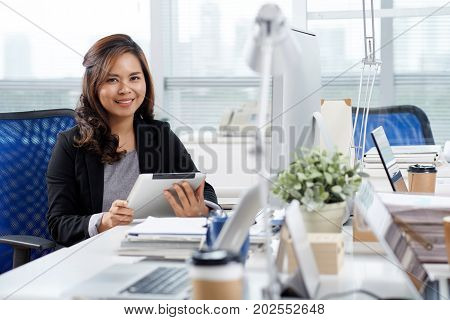 Portrait of pretty Filipino business woman sitting at her table with tablet computer