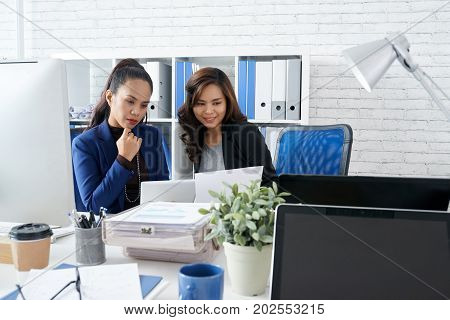 Filipino female coworkers working on project together