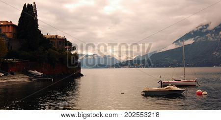 Boats on Lake Como at the sunset. Cloudy evening on a lake. Wide photo. Sunset view of the lake in Lombardy. Varenna Lake Como Italy.