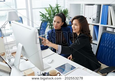 Smiling Filipino business women analyzing information on computer screen