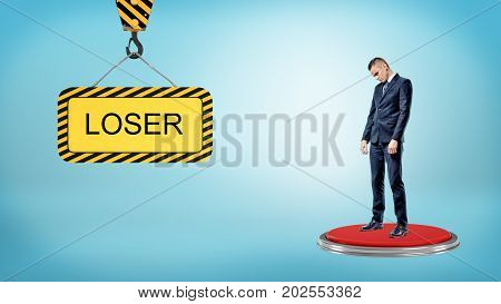 A sad businessman stands on a large red button near to a construction sign with a lettering LOSER. Troubles and difficulties. Career fail. Losers and winners.