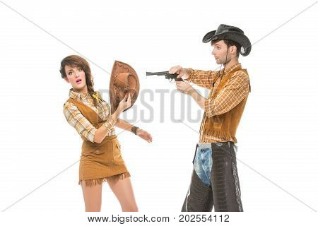 beautiful young woman and man looking like dolls. Cowboy wih gun and cowgirl isolated on white background. Copy space.