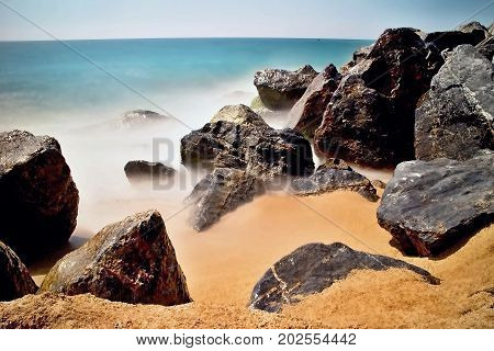 Sea waves and rocks on the beach in Malgrat de Mar, Spain. Salty sea water, waves, sun, sand, rocks and holidays summer and heat. Photo for long time