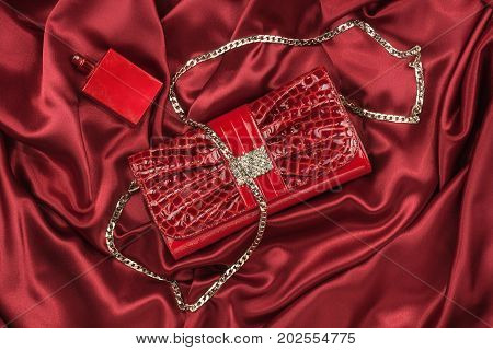 Bag of lacquered leather and red perfume lying on red silk. Handbag for women and bottle of scent top view. Accessories in modern style. Fashion and glamour concept