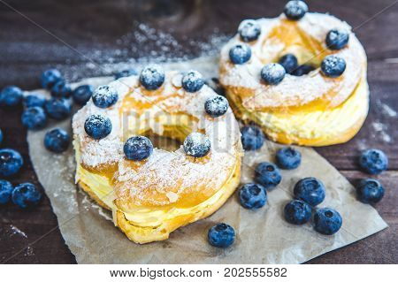 Homemade freshly baked choux pastry cake - traditional french dessert Paris Brest with whipped cream blueberry and sugar powder
