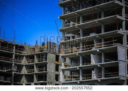 Construction concept. A new building under construction against the sky. Blue background. New urban city. Machinery, cranes and builders on scaffolding. Heavy industry and safety at work.