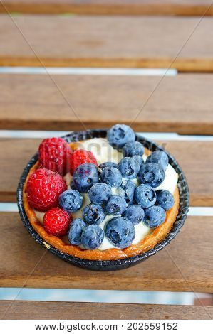 Fresh pie with mascarpone cheese topped with raspberries and blueberries on a wooden table