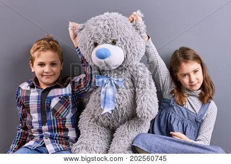 Two kids sitting with big teddy bear. Portrait of little brother and sister with big grey soft teddy bear. Kids family studio shot with soft toy.