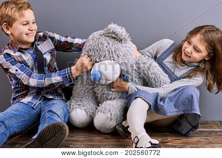 Little kids play with teddy bear. Smiling cheerful brother and sister playing with grey teddy bear sitting on wooden floor.
