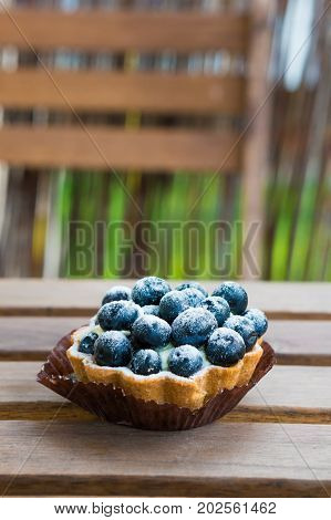 Small mascarpone pie with blueberries on a wooden table in soft focus
