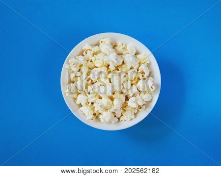 White fluffy movie theater popcorn in a bowl on blue background, top view. Cinema concept with classical popcorn