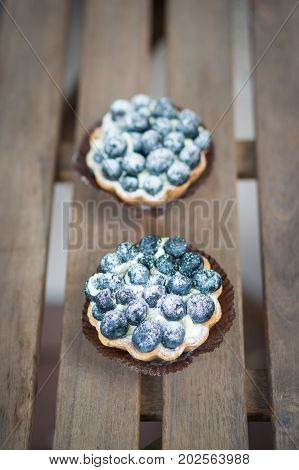 High view of two mascarpone pies with blueberries on the top on a wooden table in soft focus