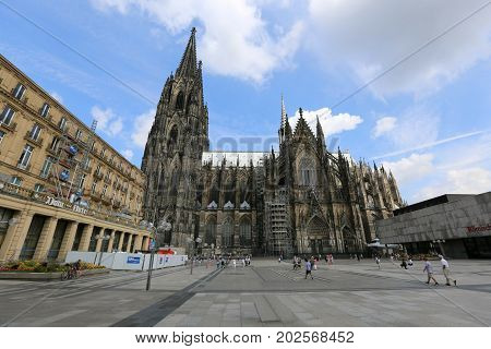 Cologne Germany - August 14 2016: Tourists in the square at the grand Cologne Cathedral. On the right part of the photo the Roman-German Historical Museum