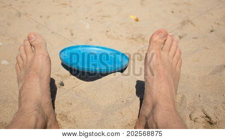flying saucer lying on the sand between his legs