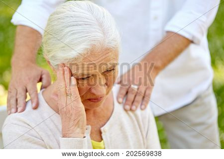 health, stress, old age and people concept - close up of senior woman suffering from headache outdoors