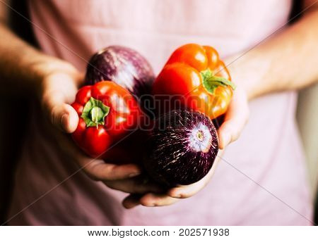 Farming business, agriculture, organic food, diet and healthy food concepts. Fresh organic red peppers in man's hands
