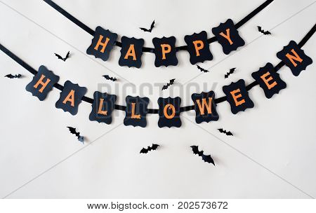 holidays, decoration and party concept - happy halloween festive paper black garland or banner with bats over white background